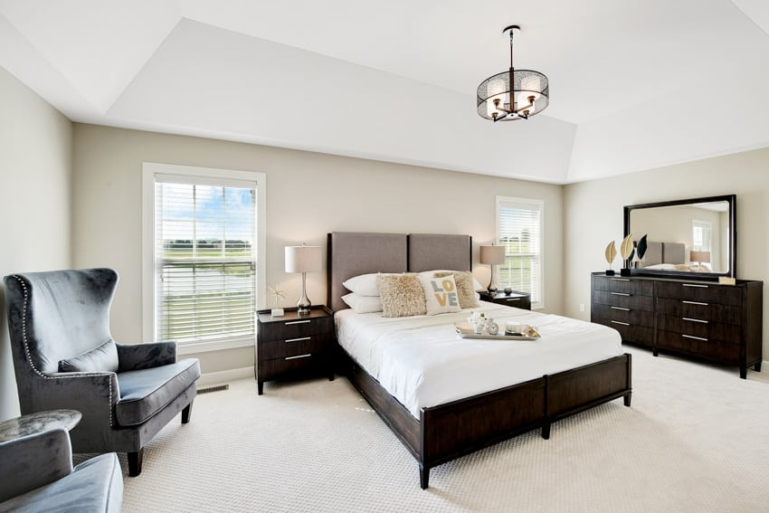 Big bedroom with dark colored furniture and hanging ceiling light