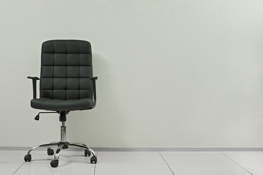Black leather office armchair against empty wall in office interior