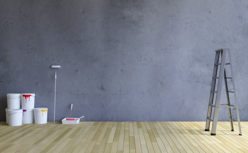 Blank cracked concrete wall and wooden floor a Ladder and painting tools and color cans on the floor