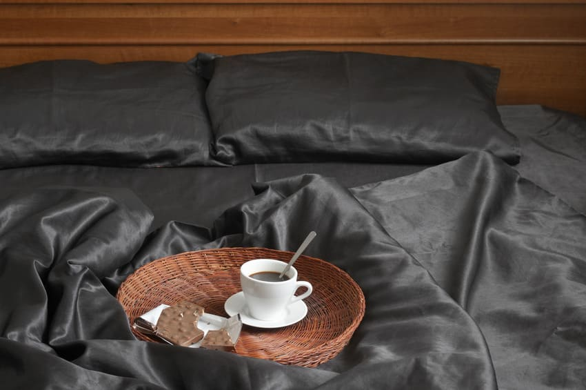 Breakfast tray on top of bed with dark silk bed sheet