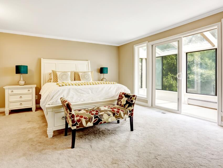 Bright bedroom with carved wood bed, carpet floors, colorful ottoman and walkout screened deck