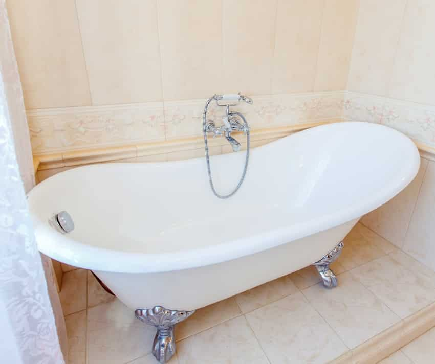 classic bathroom in beige tones with curved bathtub large beige tile and white tiles on the floor