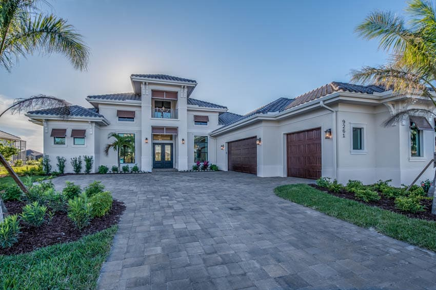 Cobblestone paver driveway to luxury house with 3 car garage