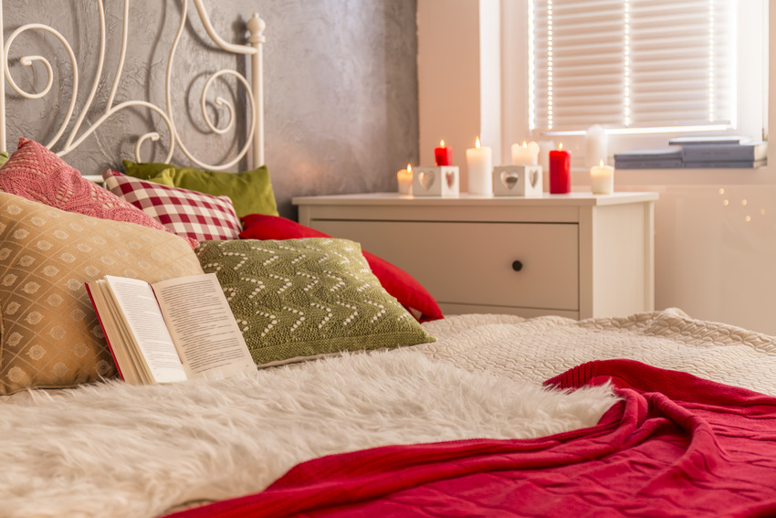 Comfy bed with stylish pillows opened book and nightstand with candles