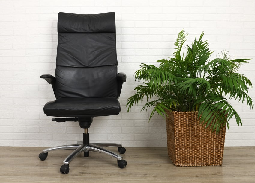 Comfy black office chair against white brick wall and gray flooring