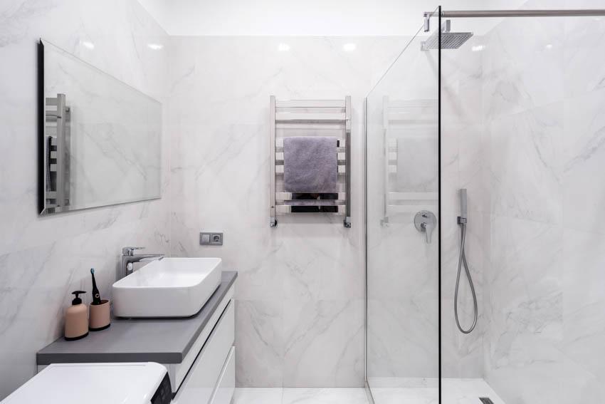 Concrete countertop inside bathroom shower area glass door mirror
