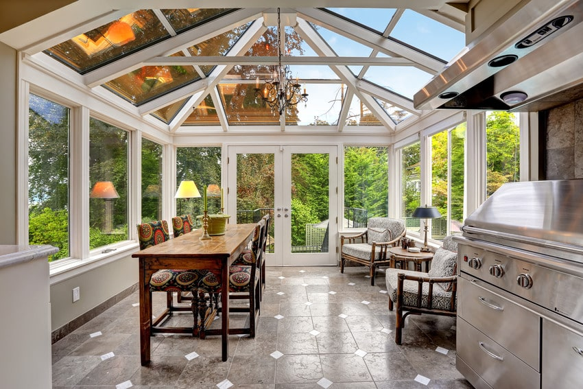 Conservatory sunroom with transparent vaulted ceiling dining table and steel bbq with hood