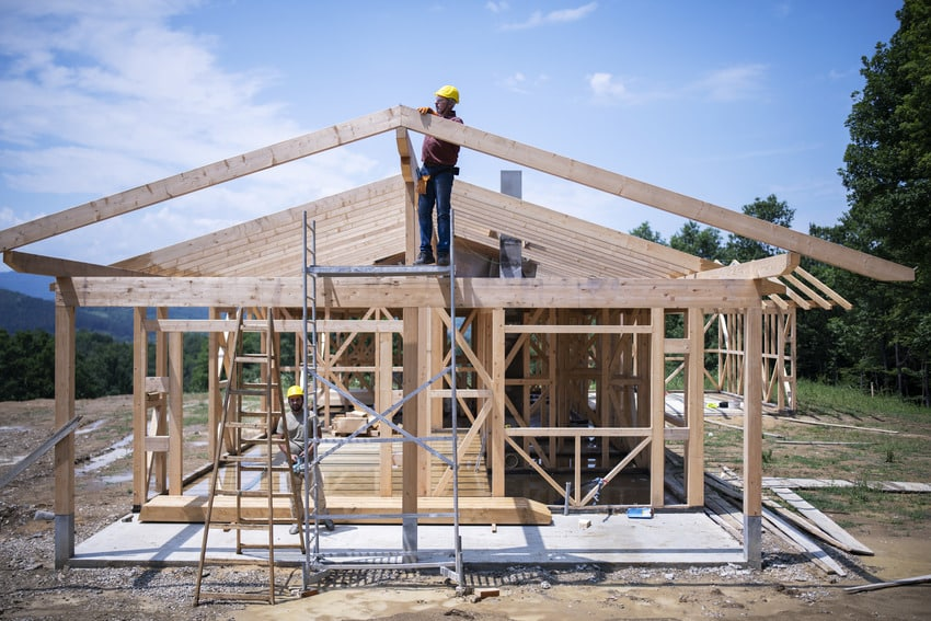 Construction workers working on roof of a house