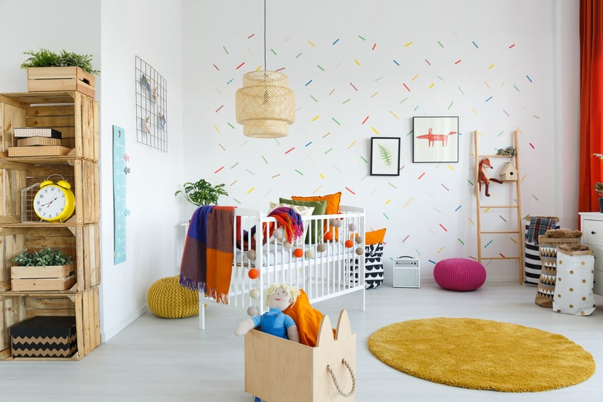 Contemporary baby room interior with stylish lighting fixture and vibrant dyed rug