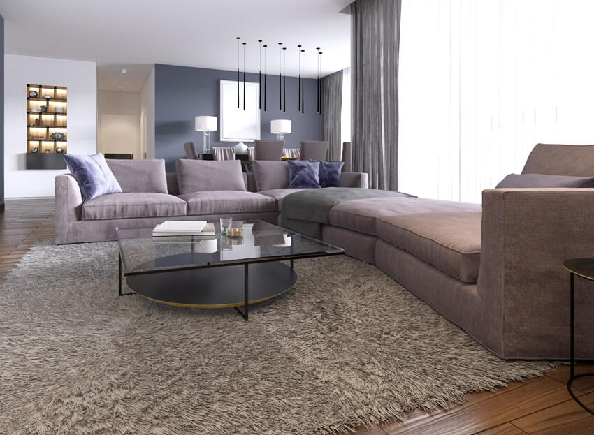Contemporary large living room with a large sofa brown carpet and dining area