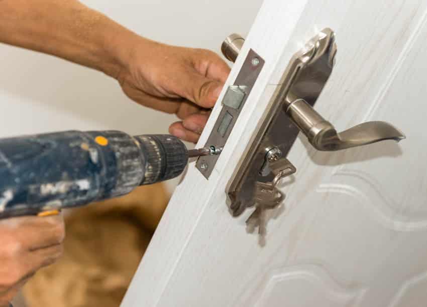 Contractor installing lock on doorContractor installing lock on door