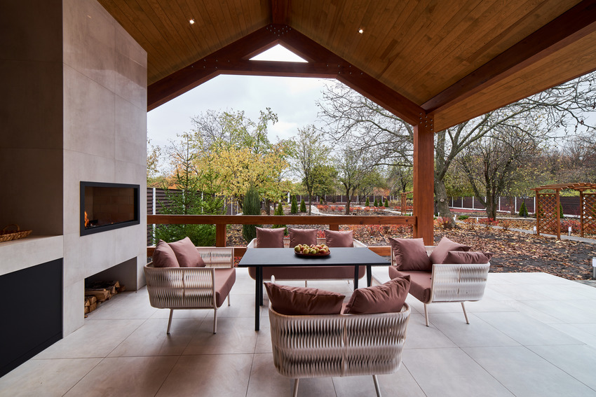 Covered patio with cozy furniture and fireplace