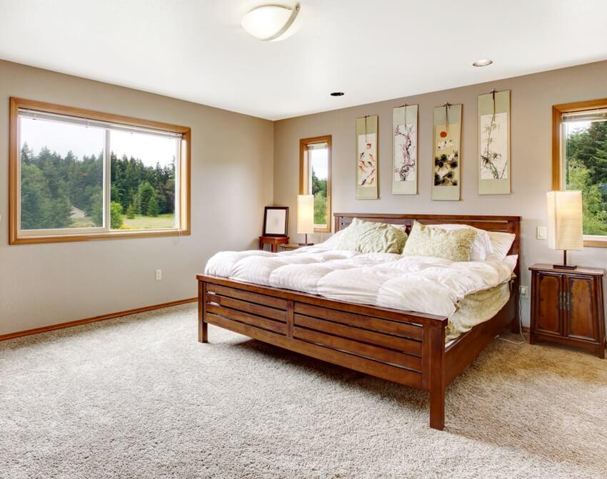 Cozy bedroom interior with double wooden bed and beige carpet floor