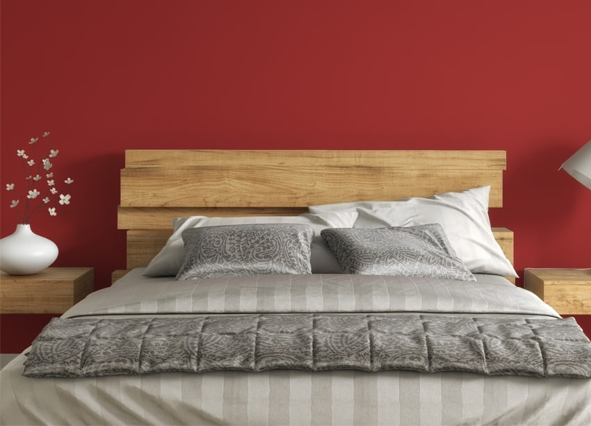 Cozy bedroom with red walls wooden bed frame and decorative plant