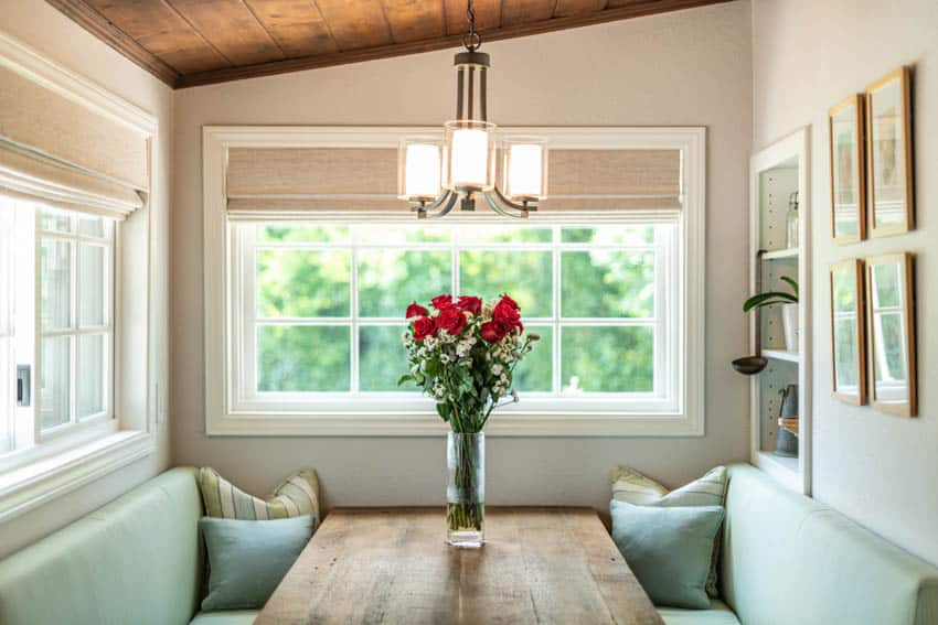 Cozy booth for eating with pillows flower vase and hanging light