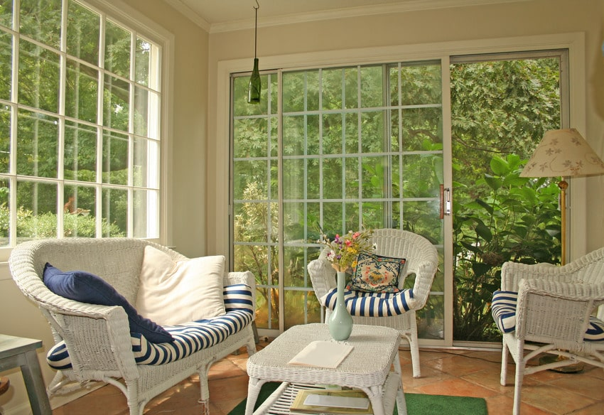 Cozy conservatory with white furniture and decorative pillows