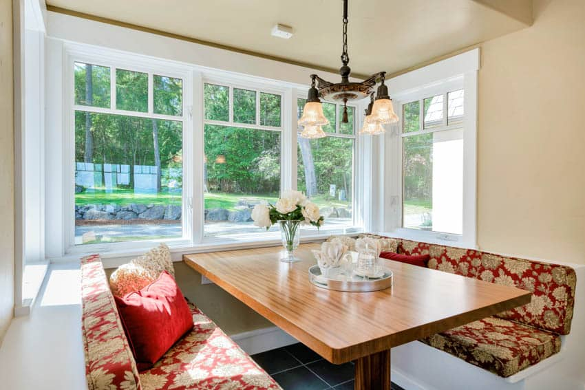 Cozy dining nook wood table white windows hanging light