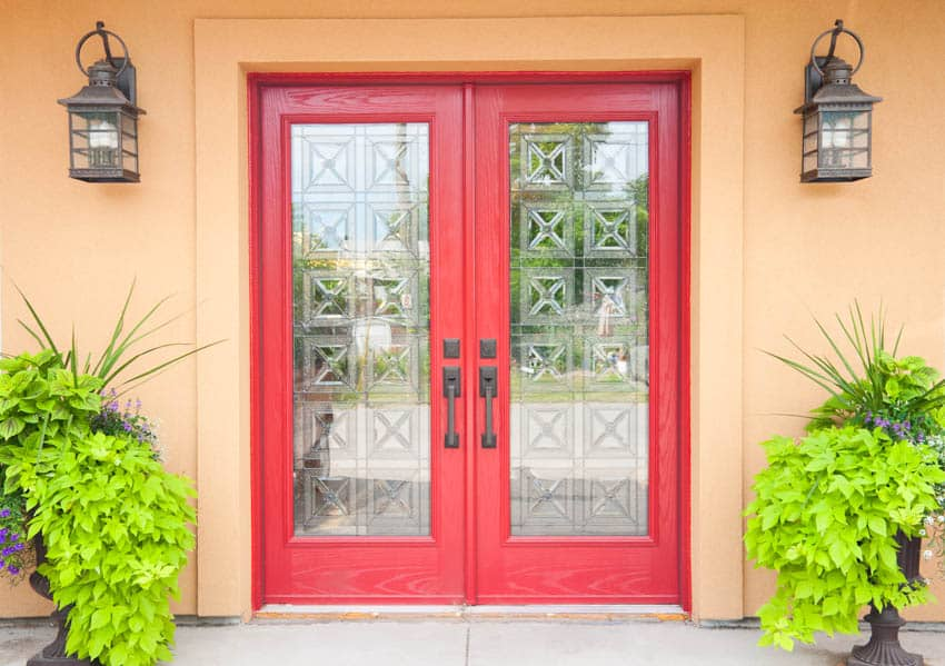 Crested glass on red door with potted plants