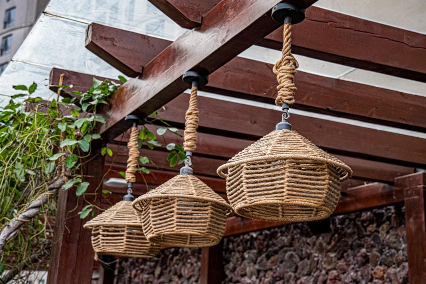 Customized pendant lighting hanging from wood pergola