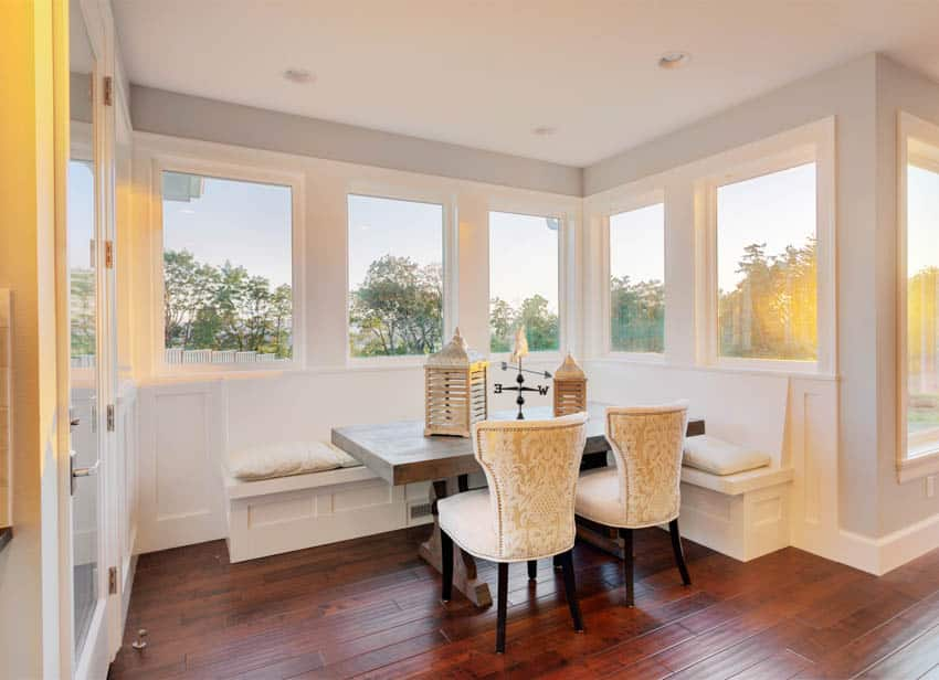 Dining area booth with wood floor and white chairs