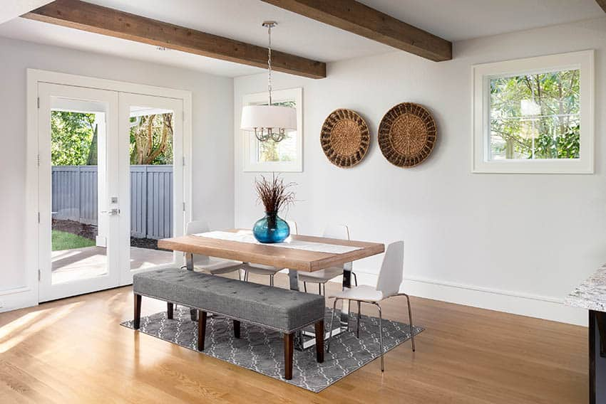 Dining room with wood beam ceiling wood flooring and glass doors to patio