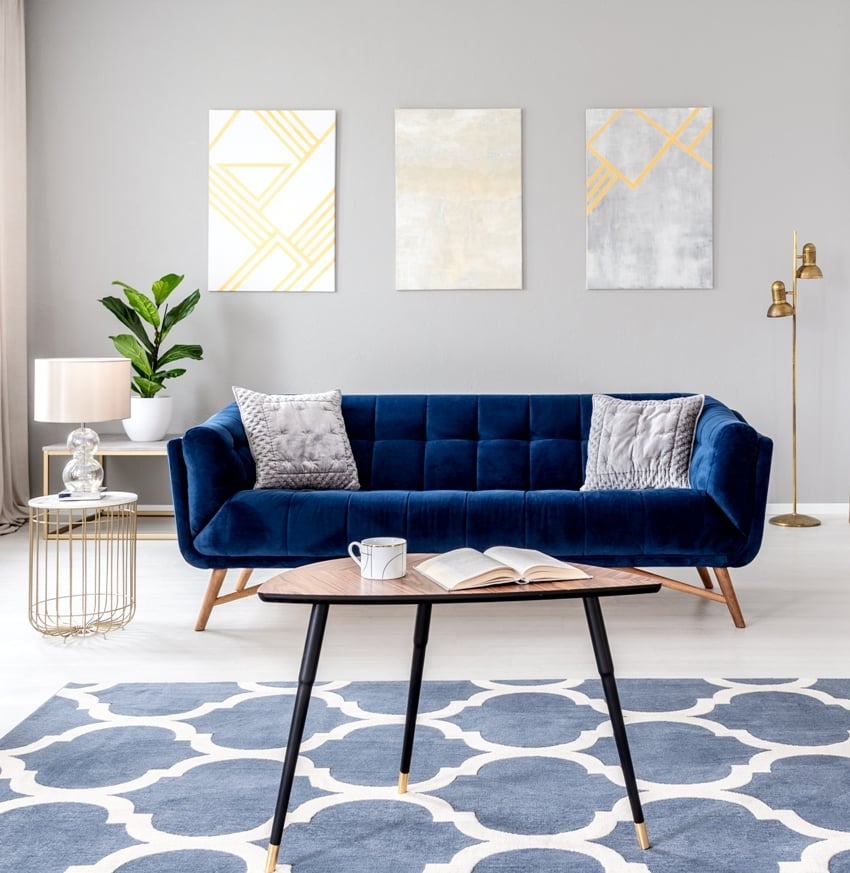 elegant living room interior with a blue sofa armchair coffee table patterned carpet and paintings on the gray wall