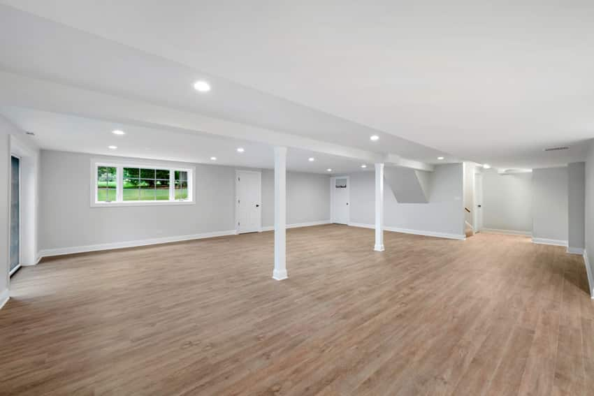 Empty basement with wood floors pillars and white walls