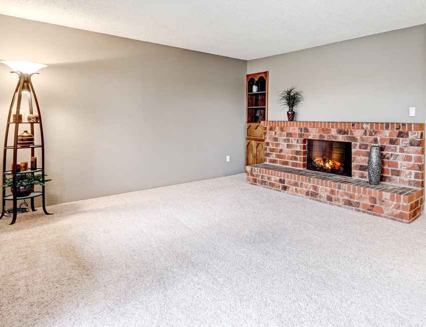 Empty living room features grey walls carpet floor and red brick fireplace