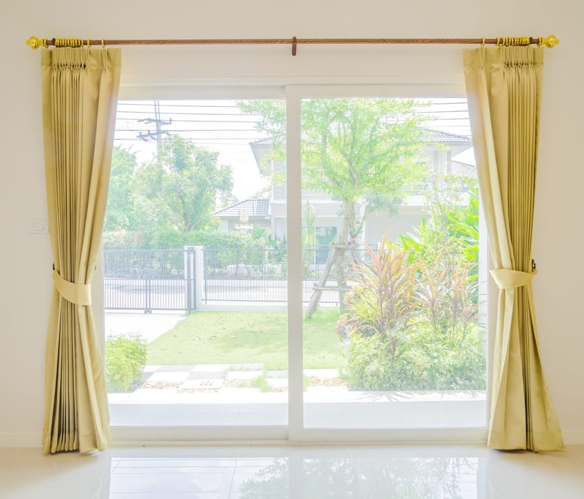 Empty room with glass doors sage green curtains and a garden view
