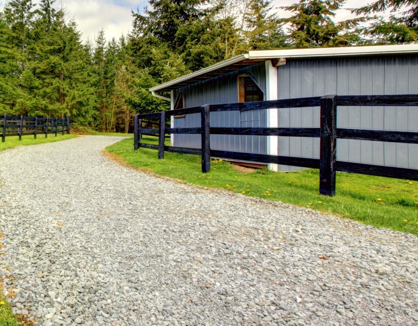 Farm with gravel driveway fence and shed with green grass