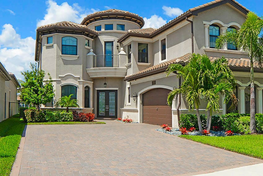 Glass and metal door luxury mansion concrete driveway palm trees