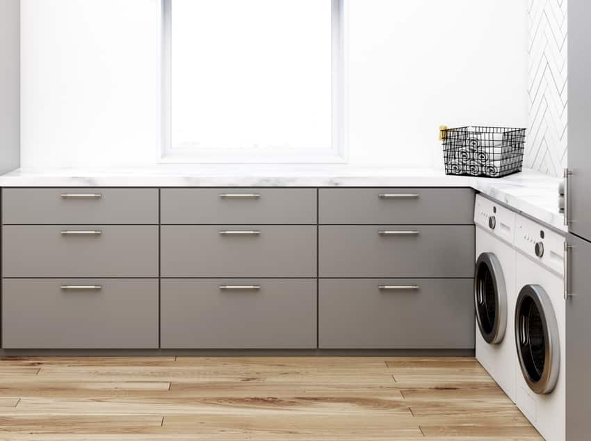 gray washroom corner with black wooden walls laminated flooring two washing machines and gray closets and countertops