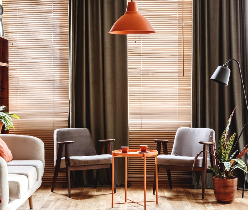 grey armchair at orange table in dark retro living room interior with drapes and blinds