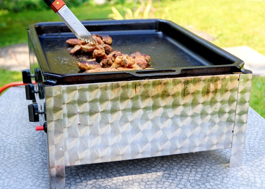Grilling chicken meat on a flat top griller