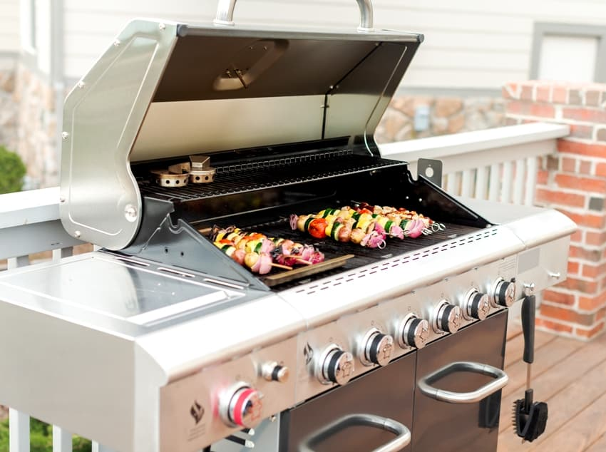Grilling veggie skewers and chicken kebabs on outdoor barbeque grill