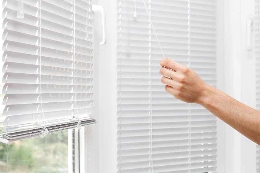 hand adjusting white cellular shade blinds in height