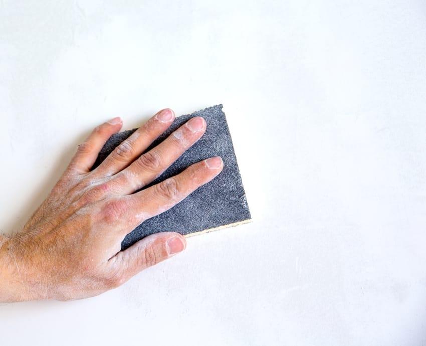 Hand sanding a wall