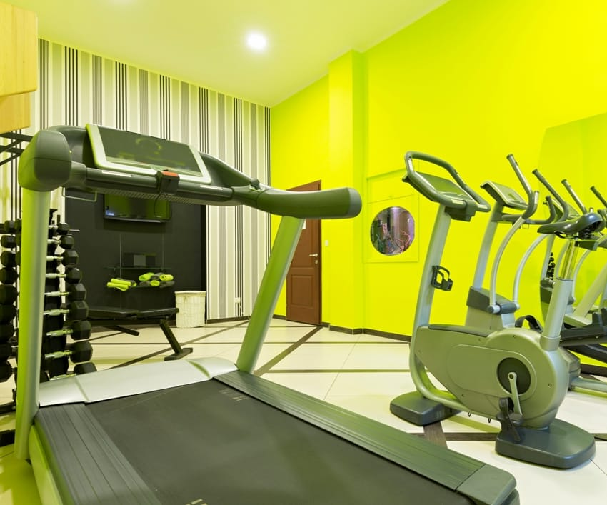 home gym in the basement with bright lime green walls