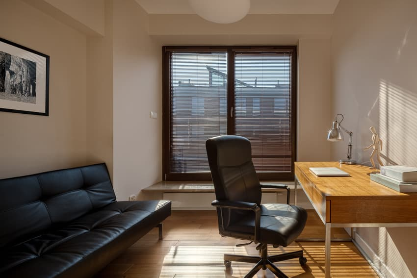 Home office with leather sofa and black vinyl chair