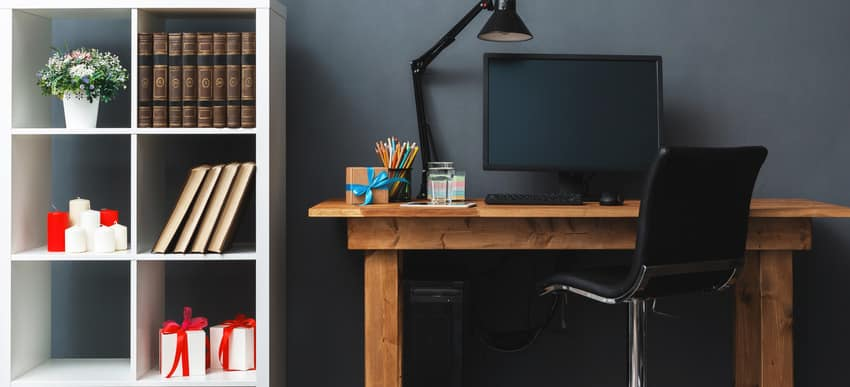 Home workplace interior with armless chair wooden desk and white bookshelves