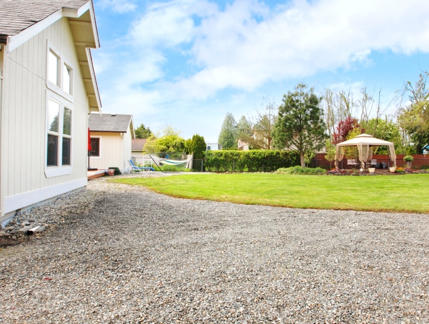 House backyard view with green lawn with gazebo and gravel driveway