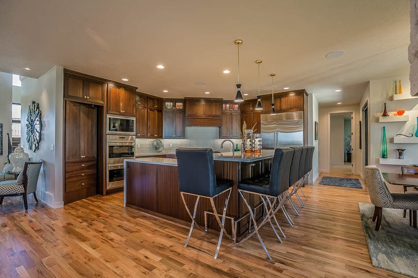 Kitchen area with wooden floors and dark trim cabinet and center island