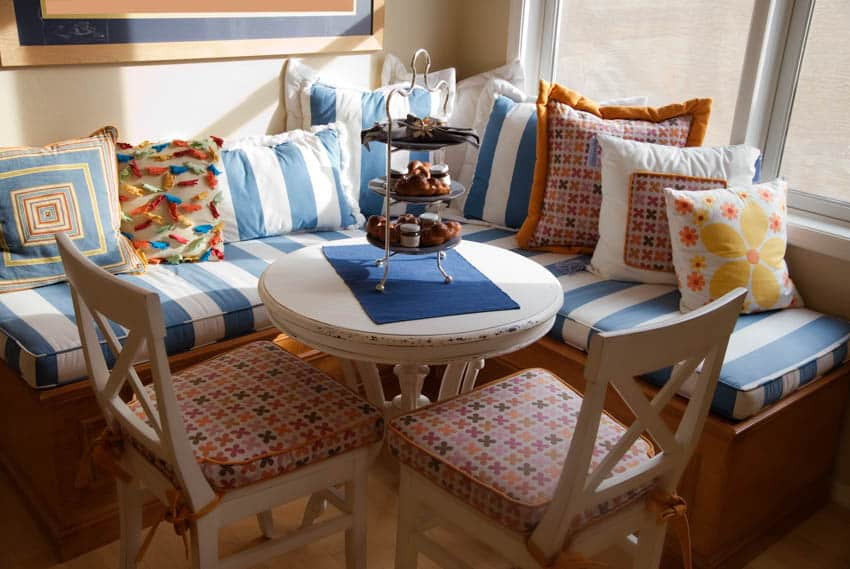 Kitchen booth with colorful pillows and small circular table