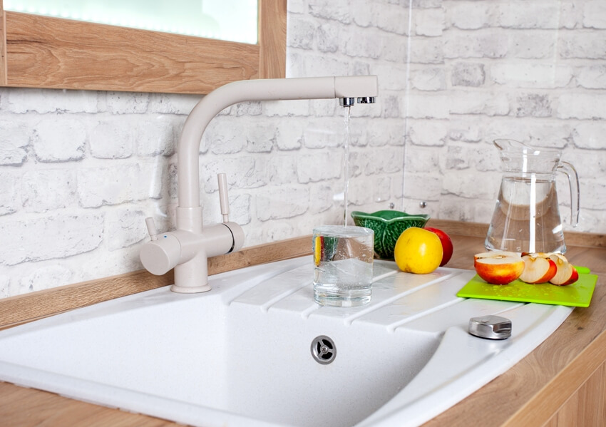 A kitchen with cast iron sink, a faucet with running water, apple slices on chopping board at the side and a glass pitcher with water