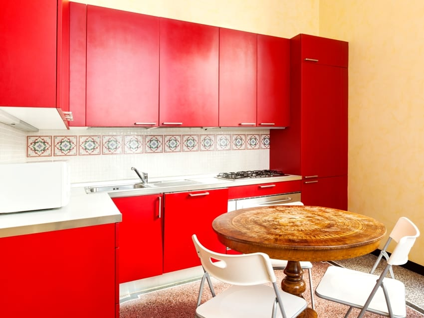 Kitchen with Cherry Red toned cabinets beige walls and dining set
