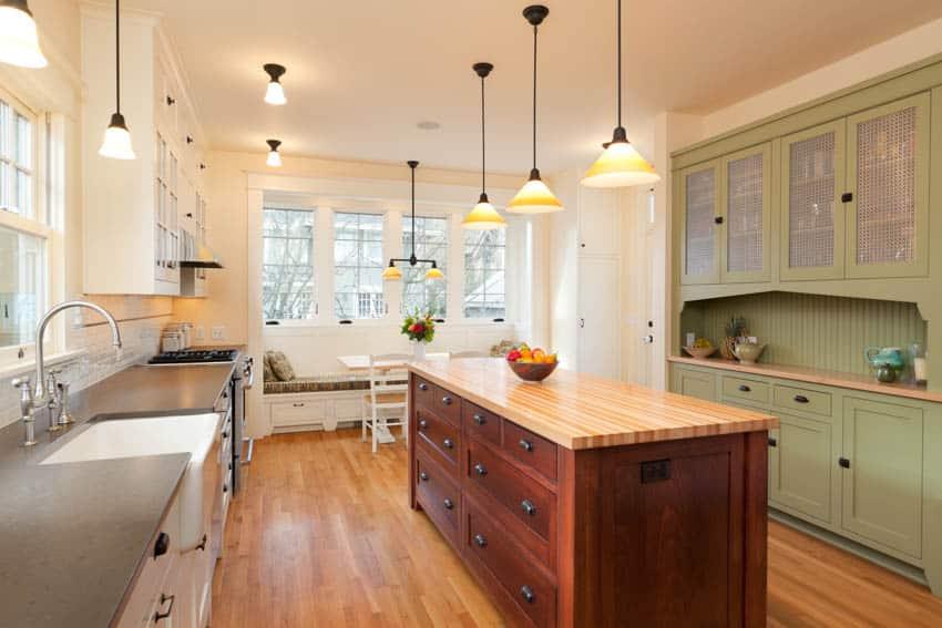 Kitchen with booth near window island wood floor cabinets pendant lights sin