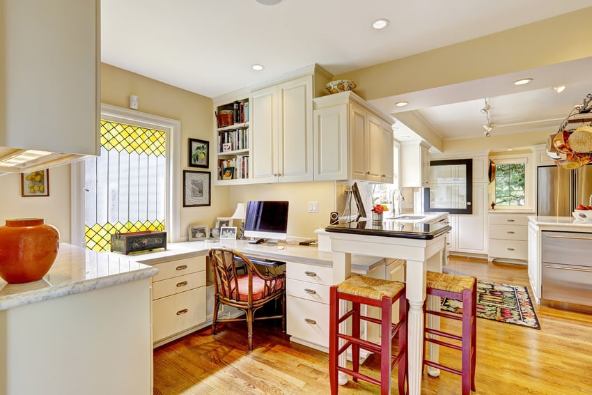 Kitchen with cream cabinets red accents and light brown walls