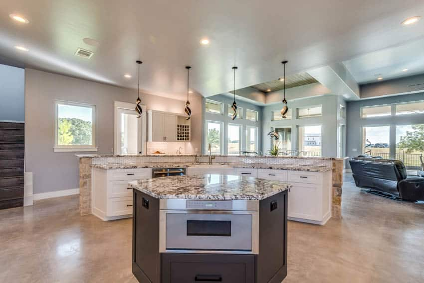 Kitchen with two tier island breakfast bar and island with oven