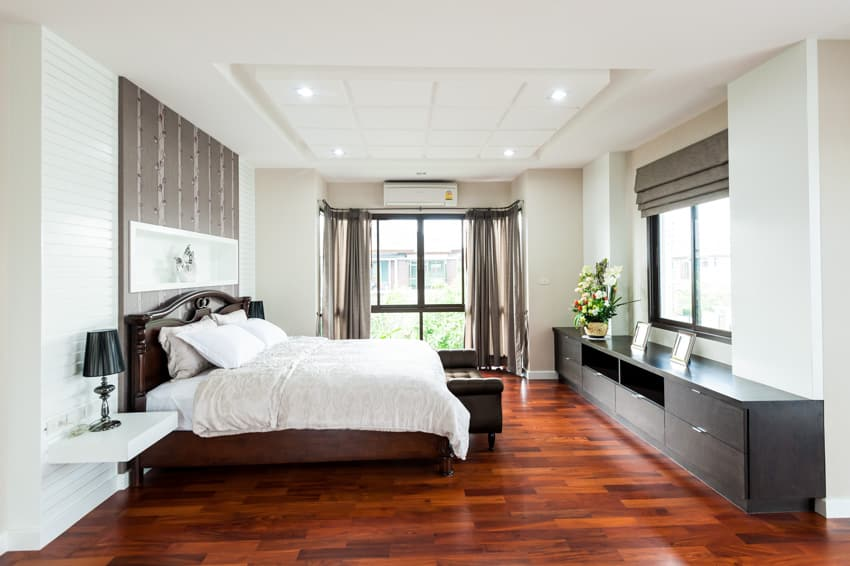Large bedroom with cherry wood floors white paint and dark furniture