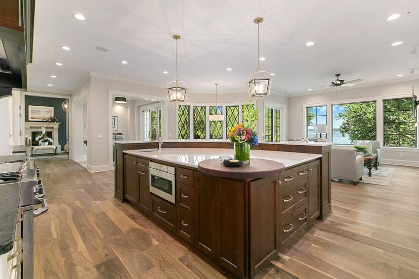 Large center island in kitchen with pendant lighting and wood floor